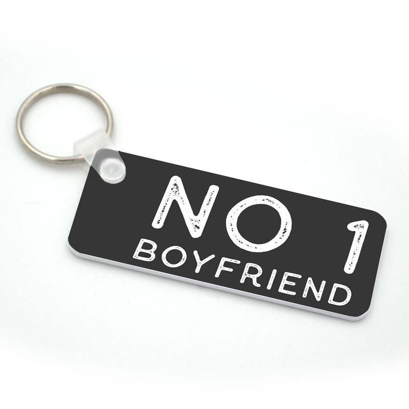 "A personalised grey keyring with the words ""No. 1 Boyfriend"" printed on it in rustic white lettering"
