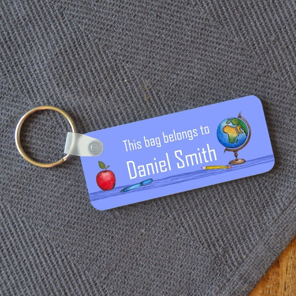 "A personalised keyring name badge in blue, the illustration features an apple and a globe and the text ""This bag belongs to Daniel Smith"" on a blue background"