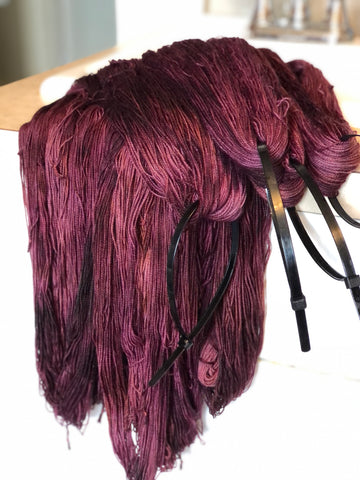 a pile of burgundy yarn hangs over a countertop.