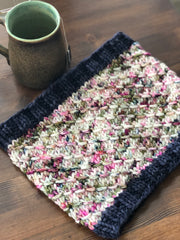 A bulky hand knit cowl with navy blue ribbing and a speckled colorway in the center sits on a table next to a mug of tea.