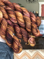 a pile a gold, bronze, blackberry, and olive colored mini skeins are being held up in the air by a woman's hand