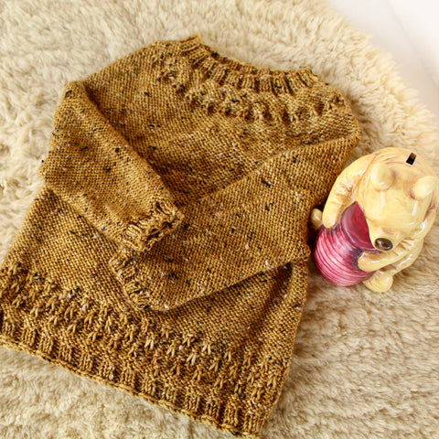 Sold hand knit baby sweater on a sheepskin with a winnie the pooh ceramic bear sitting next to it.