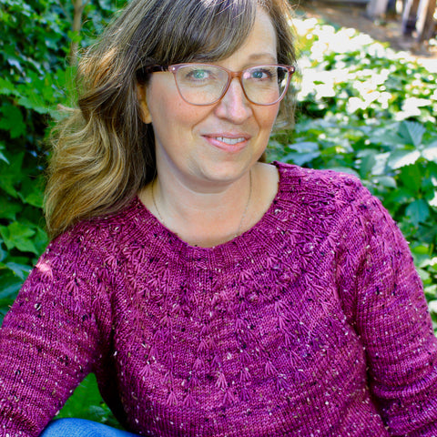 photo of a woman sitting in a bed of ivy wearing a magenta hand knit sweater. She has rosey framed glasses and long brown hair.
