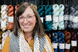 a smiling woman in front of a wall of hand dyed yarn. She's wearing rose colored glasses, a gold polka dot shirt, and and hand knit shawl.