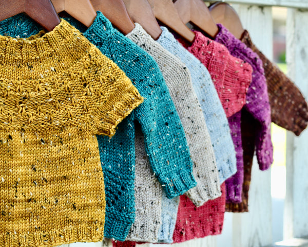 a row of gemstone colored sweaters hang on a fence. Gold, teal, sky blue, hibiscus pink, magenta, and chocolate