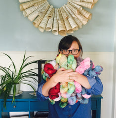 a woman stands in front of a pale blue wall hugging a pile of hand dyed yarn. She has brown hair and glasses and she is wearing a denim blue shirt.