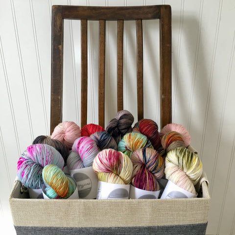 A linen basket of colorful, hand dyed yarn skeins sits on a wooden chair.