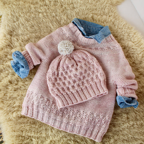 soft pink baby sweater and hat sitting on top of a sheepskin.