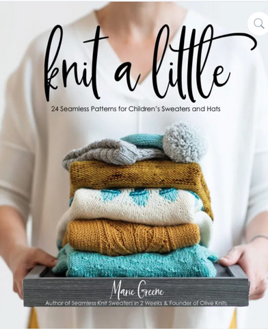 photo of a book titled Knit a Little. woman wearing a white sweater and holding a stack of tiny knitted sweaters in cream, turquoise, and gold.