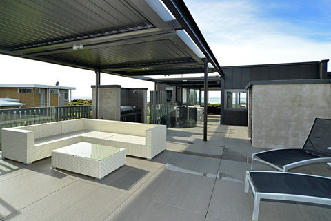 open outdoor rooftop space with white L-couch lounge set