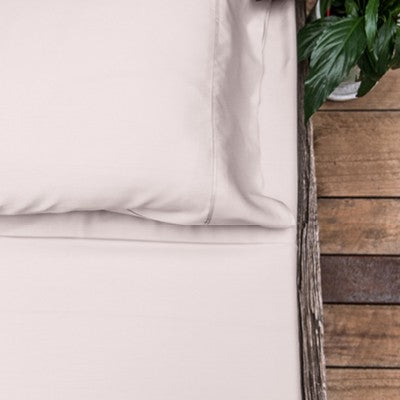 Blush or light pink coloured organic bamboo bed sheet on bed