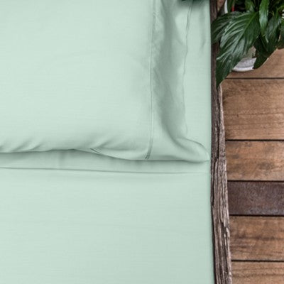 Sage or light green coloured organic bamboo bed sheet on bed