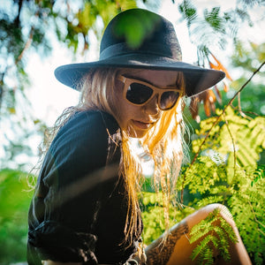 Girl with blond hair in jungle wearing Sandman sunglasses by bamb-u, Bamboo Wooden Floating Sunglasses, carbonised bamboo, UV-400 lenses
