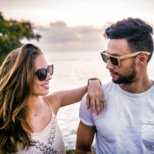 Girl smiling wearing Sienna bamboo sunglasses by bamb-u and man wearing Sammy T sunglasses, Bamboo Wooden Floating Sunglasses, brown stained frame, ideal for women, brown lens, UV-400 lens, stainless steel hinges