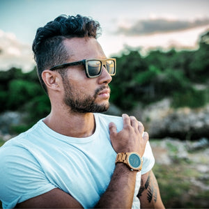 Man outdoors at sunset wearing Urban sunglasses by bamb-u, Bamboo Wooden Floating Sunglasses, distressed look, UV-400 lens, stainless steel hinge