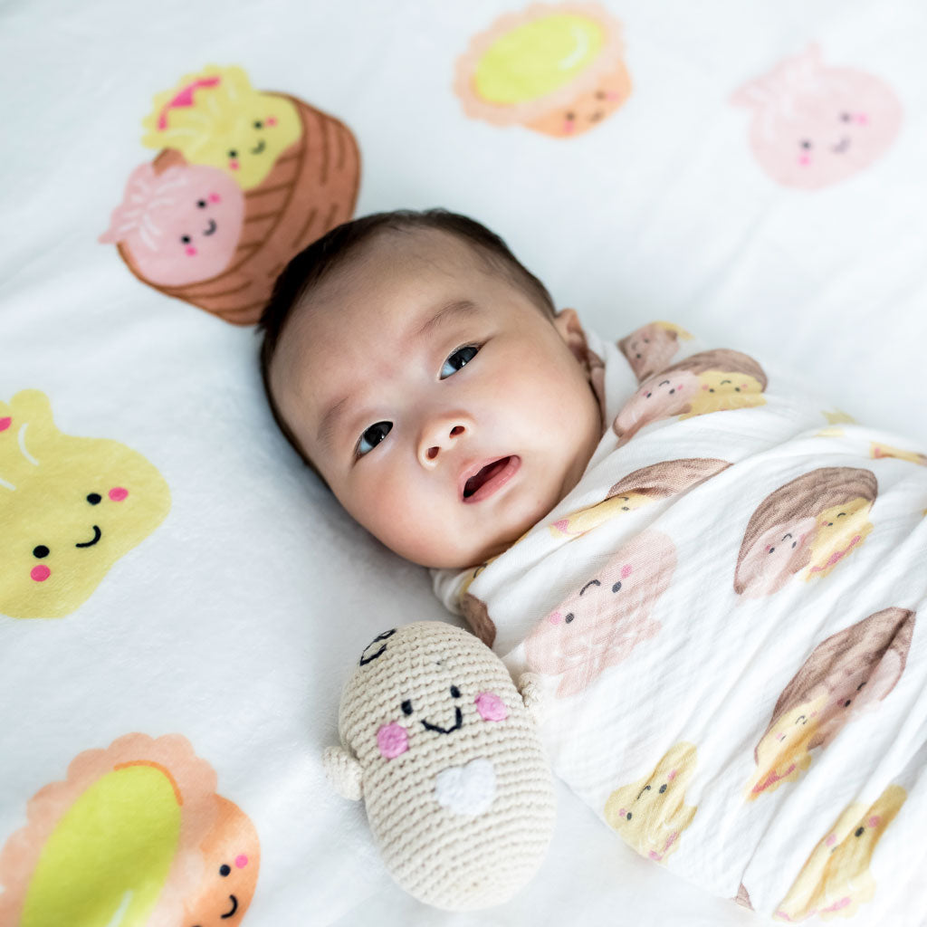 the wee bean taste of hong kong collection swaddled baby in dim sum organic swaddle and dim sum milestone blanket with fair trade bean rattle doll pebblechild