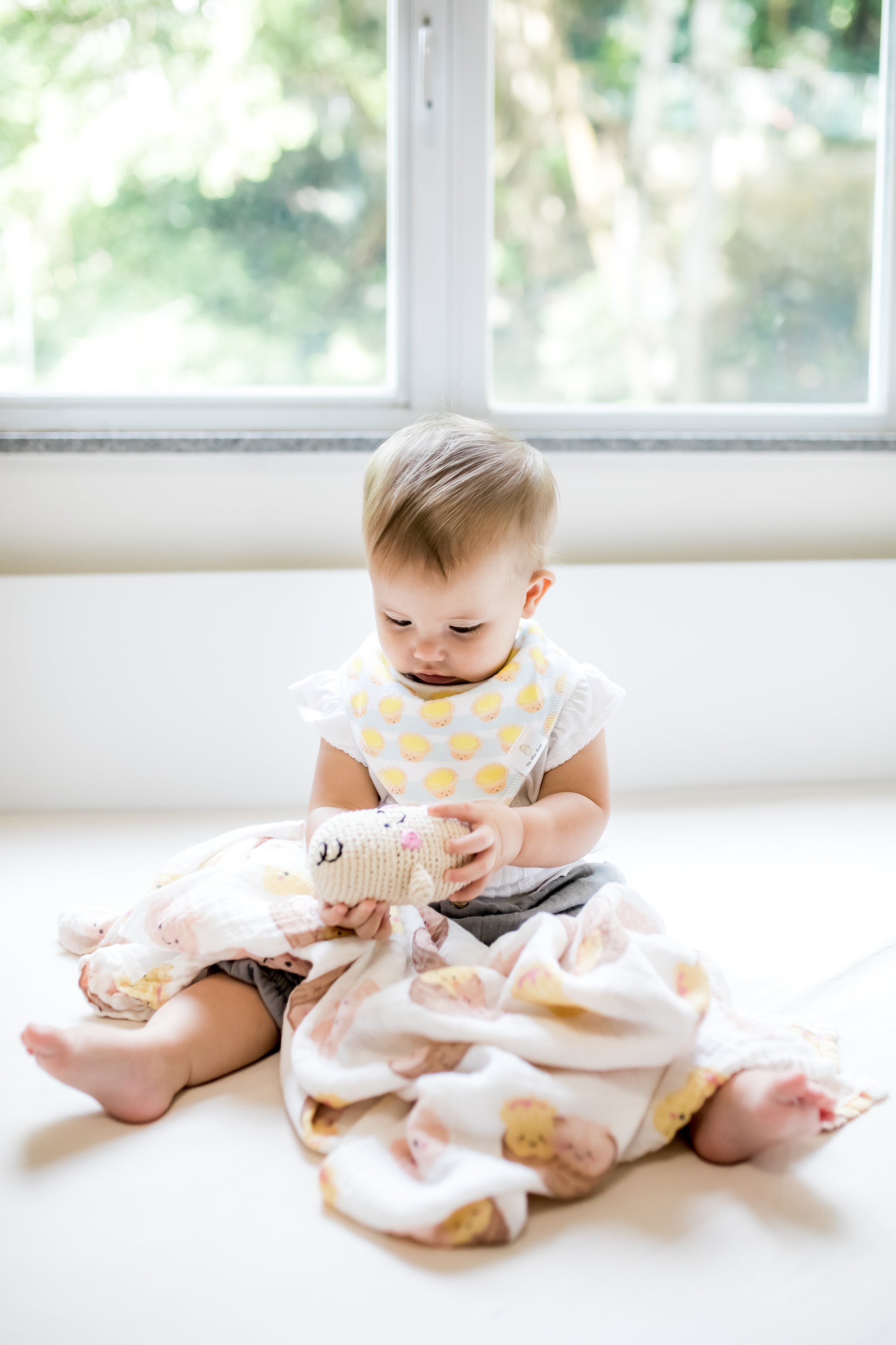 cute white baby playing with bean rattle doll fairtrade pebblechild organic dim sum swaddle the wee bean