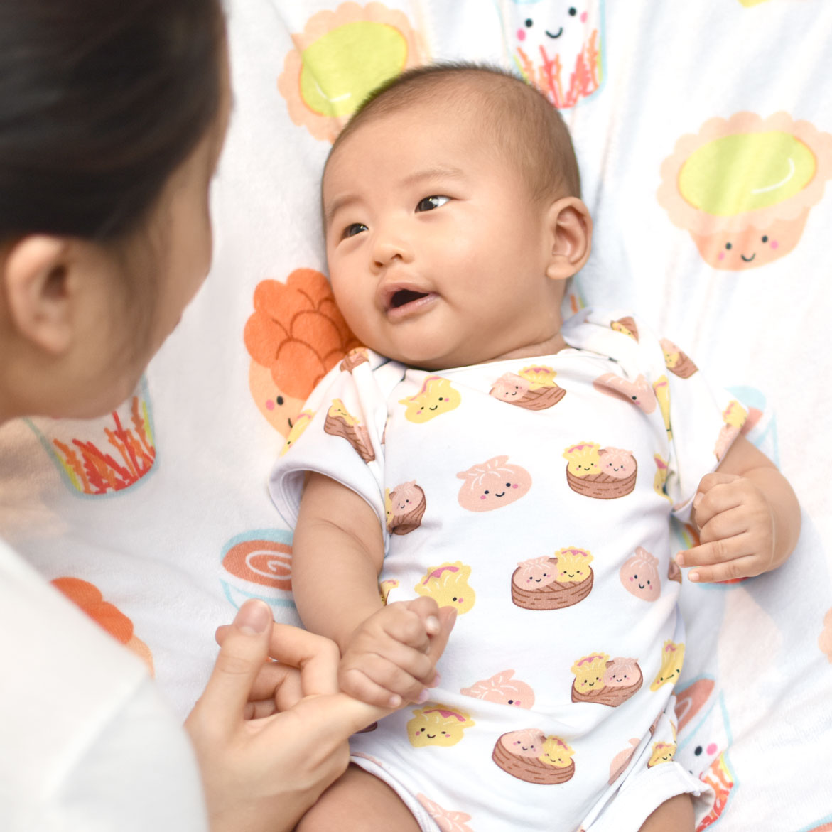 cute asian baby in an organic cotton onesie with dim sum print the wee bean