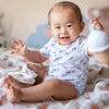 cute asian baby sitting up wearing the wee bean organic cotton onesie romper bodysuit in white rabbit candy
