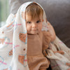 cute baby playing with the wee bean organic cotton and bamboo swaddle in boba bubble tea