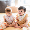 two babies wearing the wee bean organic cotton bib set in yakult and vita lemon iced tea