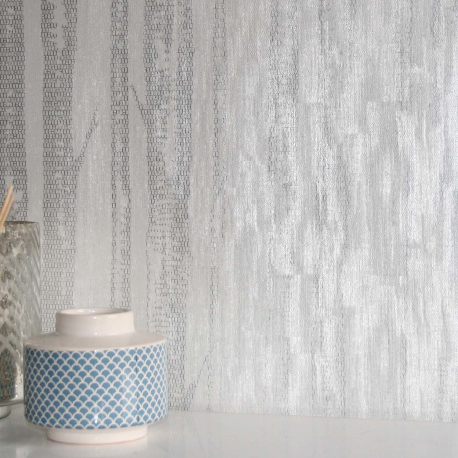 Woods' Tree Motif  Wallpaper | White & Metallic SilverThis super cool tree patterned wallpaper is reminiscent of standing in a wood. The trees look amazing with grid style pattered effect giving this wallpaper a real up to date feel and design. The white provides a matt background in which the metallic silver trees sits. It provides a simple yet decadent look. What more could you ask from a paper!h10m X w53cmStraight MatchPattern Repeat 32cm
