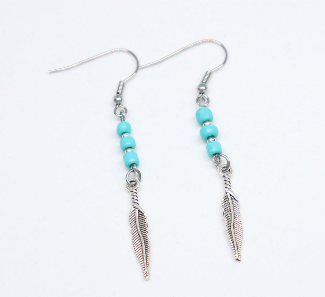 stainless steel hook earrings with blue rockery glass bead holding a feather