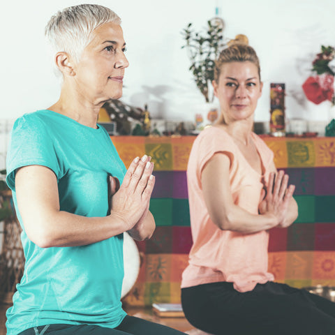 Yoga therapy specialist having one to one class with the client, retired lady who is suffering from anxiety