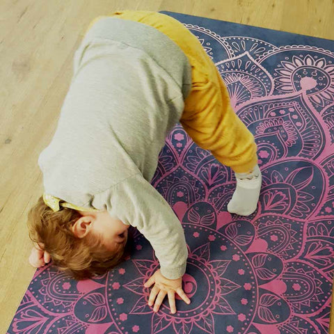 two years old boy is doing downward dog kids yoga pose on Zenagoy Mandala yoga mat