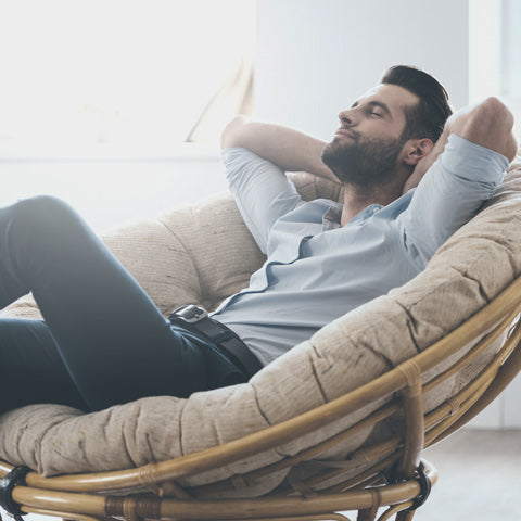 Happy men is doing nothing on this armchair and smiling