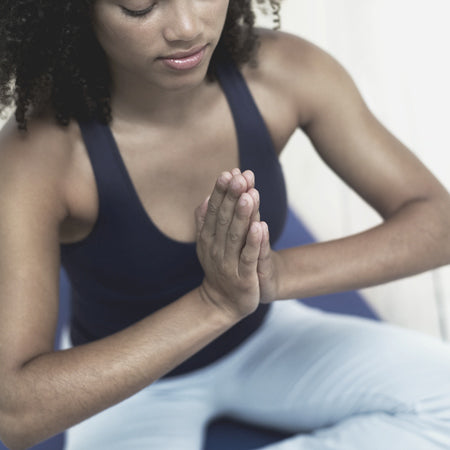 Woman holding her hands in namaste position for meditation