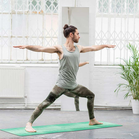 Ashtanga yoga teacher on non slip good grip green yoga mat in Warrior 2 pose