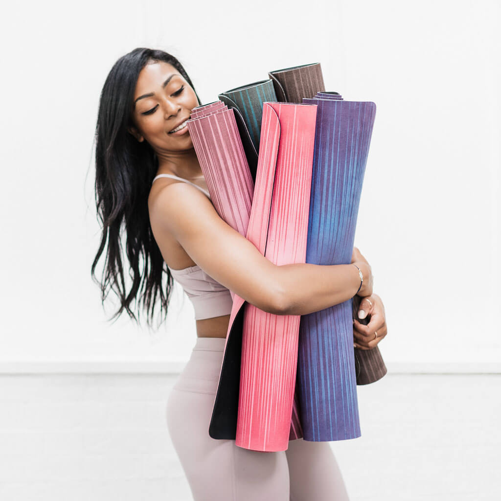 Yoga teacher is holding microfiber top yoga mats for intensive yoga practice