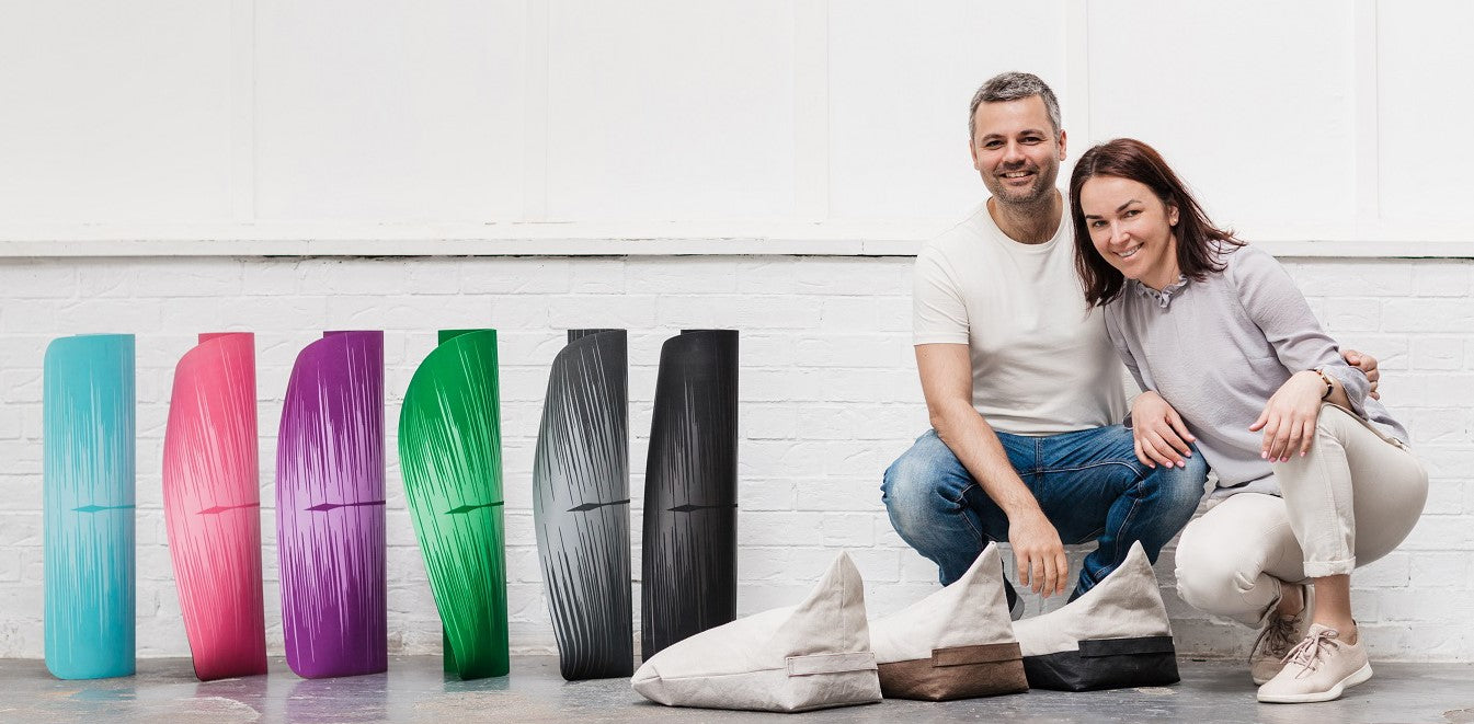 Picture of the founders of ZENAGOY yoga brand. Ben and Jurgita with the collection of colorful yoga mats