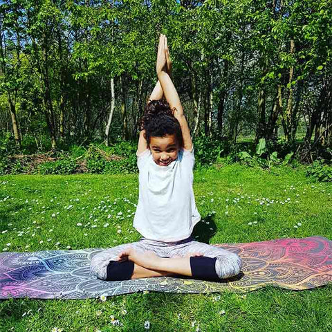 Little girl yogini practicing yoga on Rainbow Mandala Zenagoy yoga mat in the park