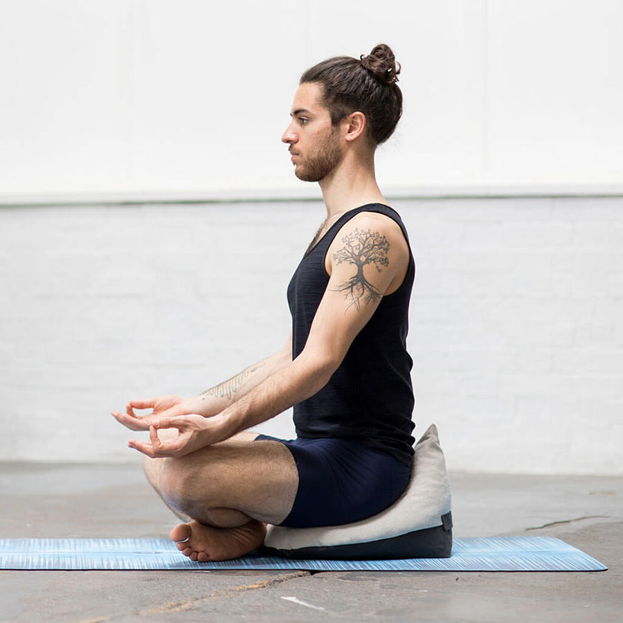 London yoga teacher meditating on OMigo floor cushion