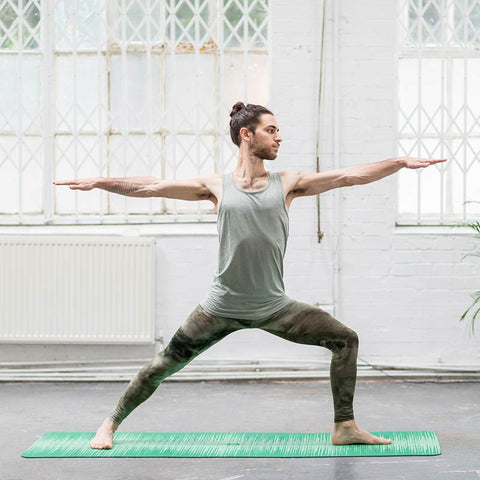 Man in yoga pose warrior 2 on green PU yoga mat