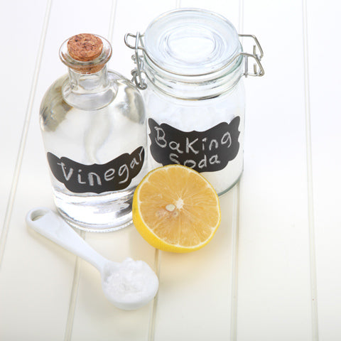 A jar of soda, spoon, lemon and water - ingredients for making a spray for cleaning a yoga mat