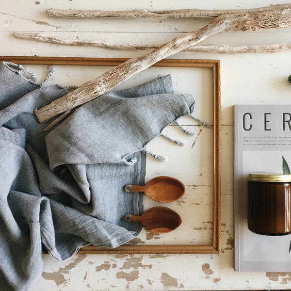 A Flat Lay image including some of Farmer's Daughter Interiors favourite products such as the Turkish towel, the Cereal Magazine, olive wood decor spoons and a candle.