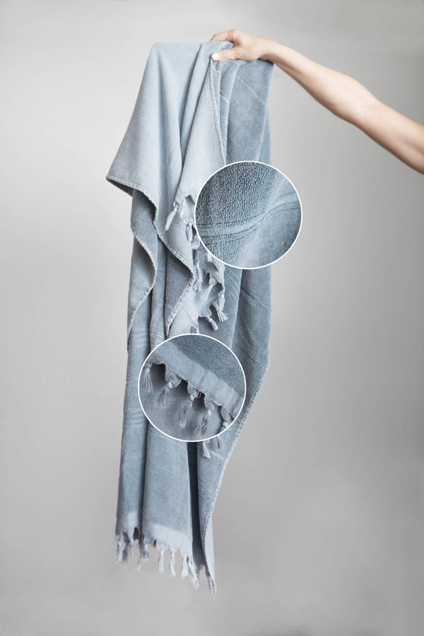 A grey Turkish Towel with fringed tassel edging. One side is smooth cotton and the other is looped cotton terry. Beach Towel, bath towel, travel towel. Shop online. Local Swift Current SK Shop. Prairie Living. Modern , bohemian.