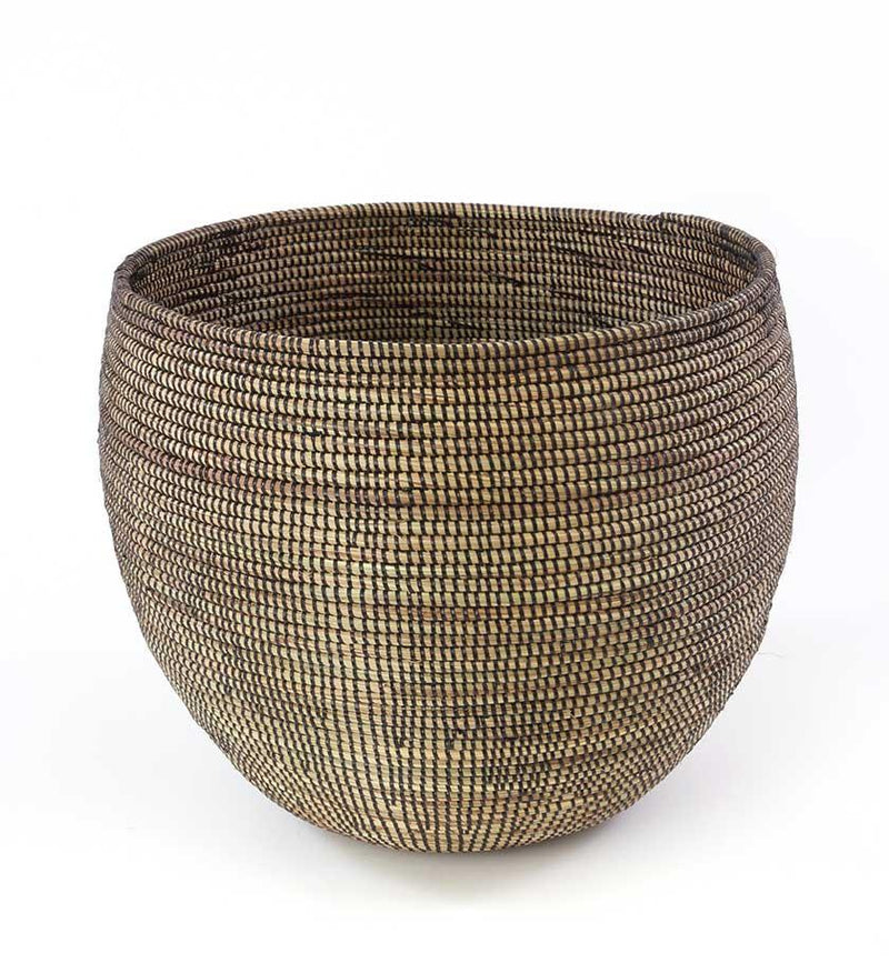 A round hand woven, tan basket that is made from cattail stalks interwoven with black plastic. For storage use to store household items, blankets, throws, shoes, clothes. Shop online. Shop Local Swift Current SK. Modern prairie living. Home decor. Handpicked homewares.
