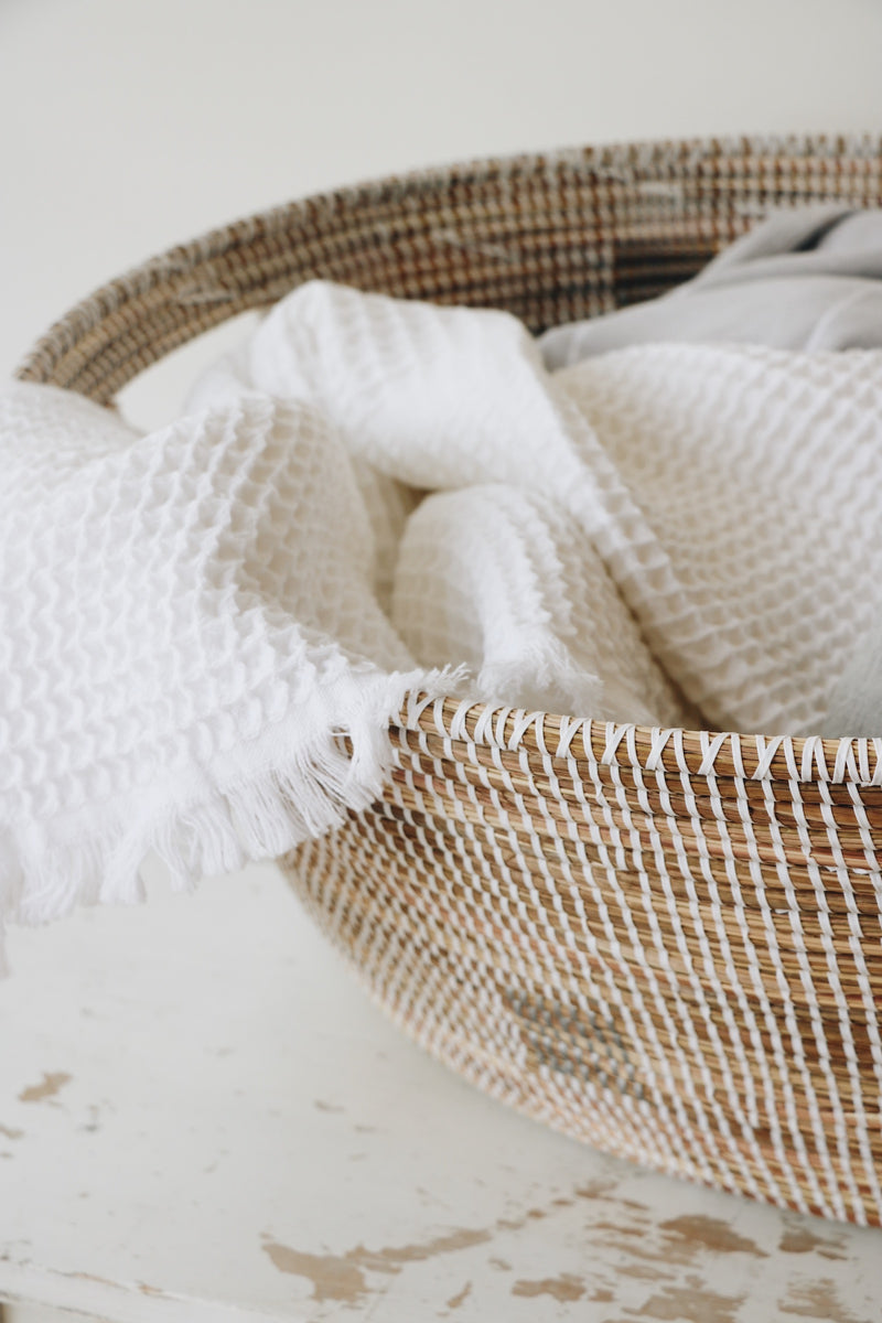 A basket being used for laundry with a white waffle textured towel in the basket and pouring over the side. The Home Quarter Shop.Swift Current Saskatchewan, Shop local. Candles, home decor, bedding, handsoap, towels, baskets