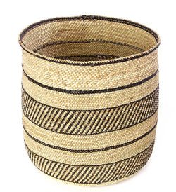 A handmade woven basket that is tan in colour with black horizontal stripes. Made from milulu grass and natural dye. Handmade basket. Handcrafted basket. Fair trade basket. Shop online. Shop local Swift Current SK. Home decor. Modern Prairie living. Handpicked homewares.