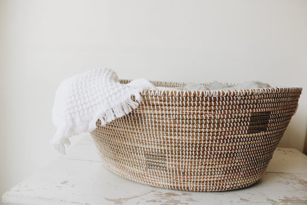 A laundry basket with a white waffled texture towel peaking out on the side. The Home Quarter Shop Swift Current Saskatchewan. Shop local. Saskatoon, Regina, Home Decor Shop.Handmade, Ethically made goods. Modern Bohemian Decor. Modern Farmhouse decor. Candles, handsoap, towels, baskets, artwork