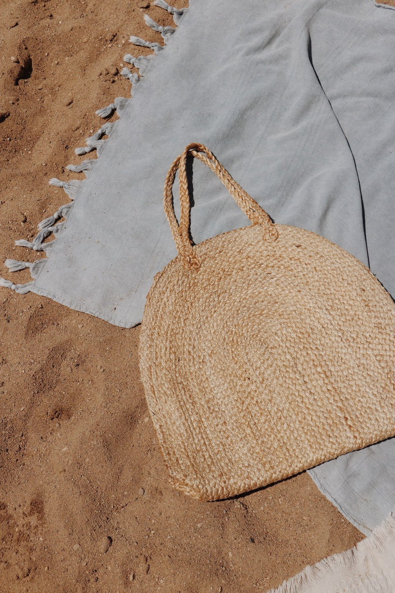 The Home Quarter Shop. An image of a straw tote bag laying on a turkish towel on the beach. Home decor, area rugs, wallpaper, towels, baskets, candles, coffee, home fragrance, blankets, throw pillows