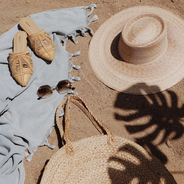 The Home Quarter Shop. An image of a sandy beach with a turkish towel laying on the sand with sunglasses and a straw hat. Home Decor, area rugs, wallpaper, beach gear, tote bag, baskets, home fragrance, candles, coffee