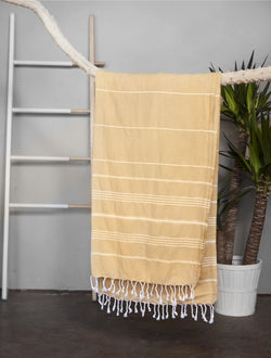 Mustard coloured with white stripes Turkish towel with white fringed tassel trim. Beach Towel, Bath Towel. Made from 100% Turkish Cotton. Shop Online. Local Shop in Swift Current SK. Home Decor