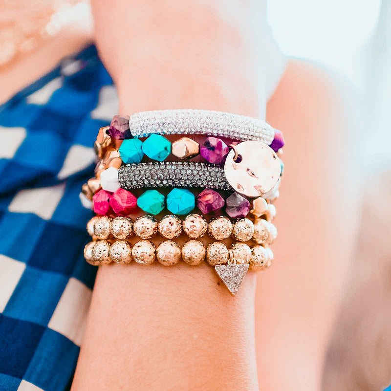 Beaded stretch bracelet stack with gold and colorful gemstone beads and pave bar, druzy triangle, and gold plated disc details