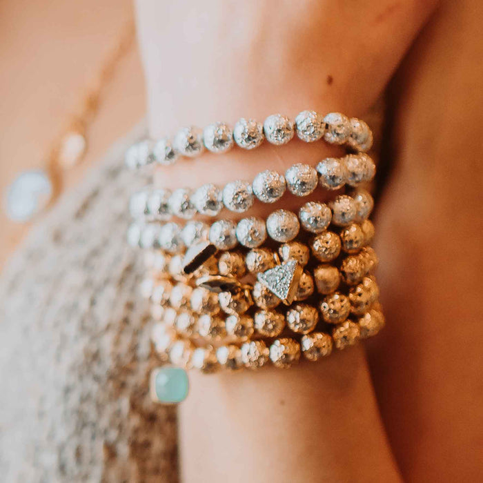 Image of model wearing gold and silver plated lava rock beaded stretch bracelets with druzy triangles and gemstone drops