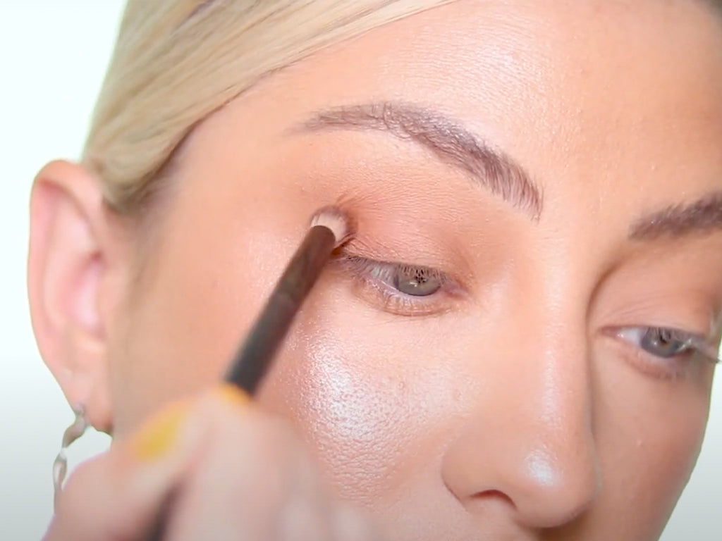 Applying a darker eyeshadow into the crease of the eyes.